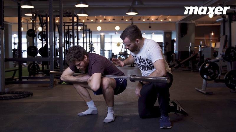 Siddende i bundpositionen af en squat kan du udfordre din ankelmobilitet med stang.