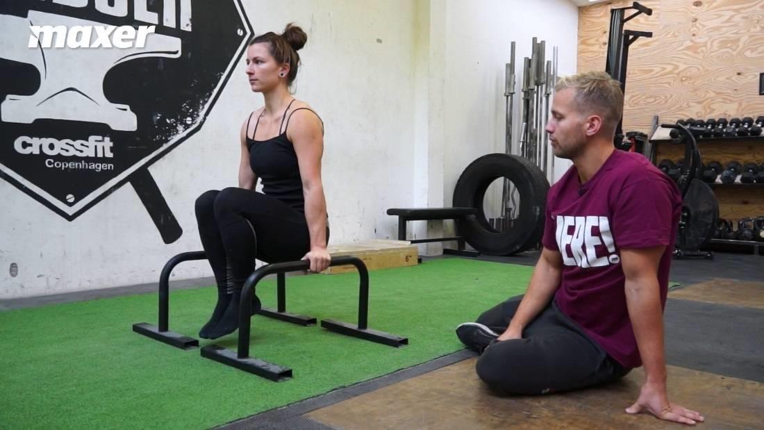 Tuck L-sit udføres med bøjede ben for at gøre vægtarmen kortere og er dermed lettere.